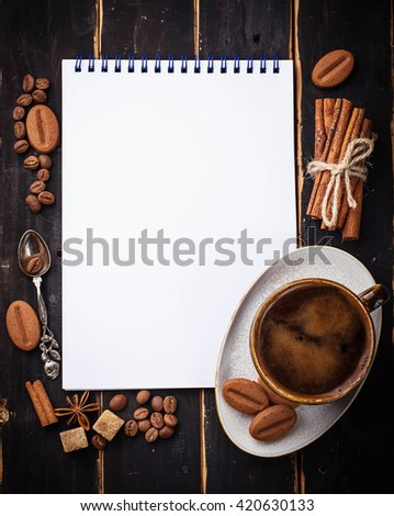 Coffee, sugar, cinnamon, cookies and open notebook. Selective focus, space for text