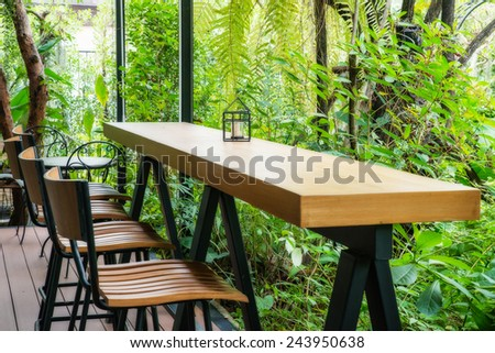 Coffee table and chair in the green garden. - stock photo