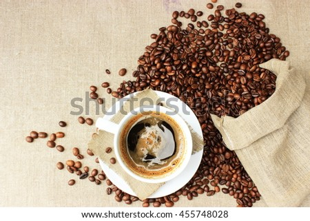 Coffee theme:parcel full of brown grains on textile linen background with cup of hot tasty espresso with copy space. Rustic decor elements, vintage design - stock photo