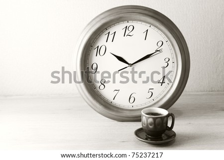 Coffee time: cup of coffee and clock. Sepia. - stock photo