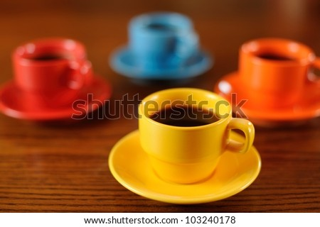 Coffee Time for Four. Group of four brightly-colored demitasse coffee cups on a wooden table. Shallow DOF. - stock photo