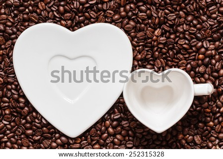 Coffee time. White empty cup and saucer in heart shape on roasted coffee beans background. Top view - stock photo