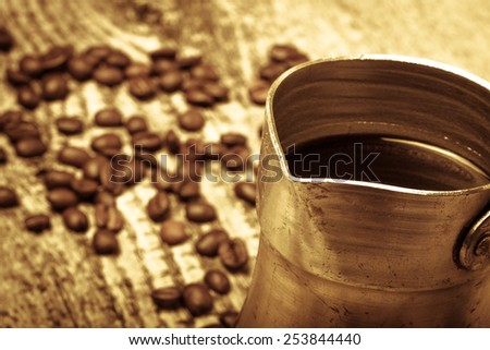 Coffee turk and coffee beans on old gray wooden table. Toned.