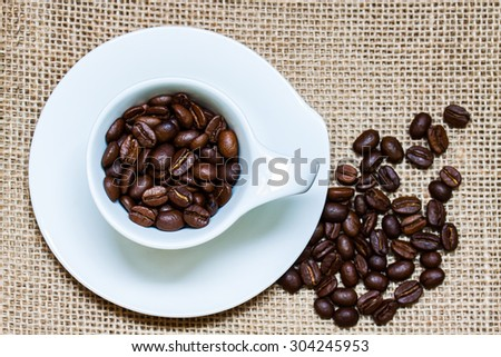 Coffee wallpaper, background, grains of coffee plant in white cup with saucer and on burlap, sackcloth texture. Coffee  time.