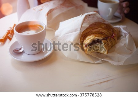 Coffee with a chocolate croissant on the table in the coffee shop. - stock photo