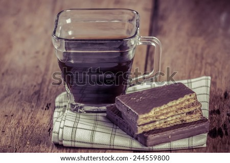 coffee with biscuit chocolate on wooden table - stock photo