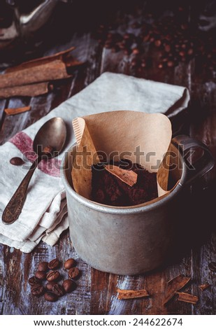 Coffee with cinnamon in iron vintage cup on wooden background. Toned image