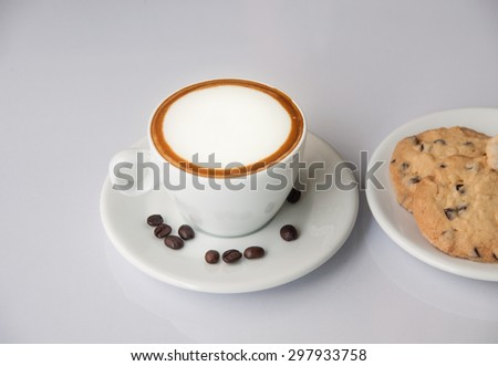 Coffee with cream in white cup and cookies on saucer