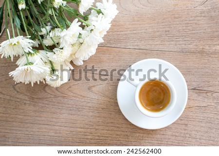 Coffee with flowers on wooden table - romantic tone. - stock photo