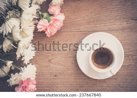 Coffee with flowers on wooden table - vintage tone. - stock photo