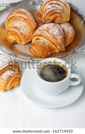Coffee with fresh croissants on wooden table still life