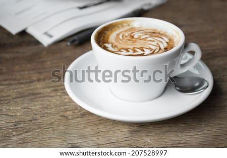 Coffee with latte art in cup on wooden table.