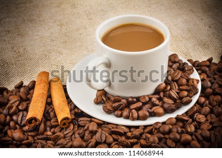 Coffee with Milk in a Ceramic Cup on a Saucer, Roasted Beans and Cinnamon Sticks on Burlap Background
