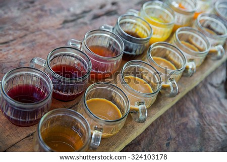 Coffee with multiple assorted types and flavors of coffee and tea in identical mugs for degustation on farm, Bali island - stock photo