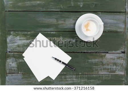 Coffee with note or paper on wood background