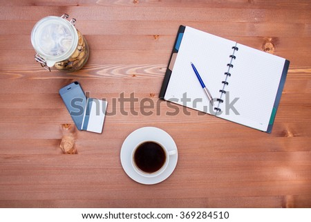 Coffee with notepad and pencil on wood table