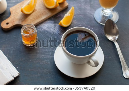 Coffee with orange juice, orange slice and marmalade on a breakfast table with newspaper  - stock photo