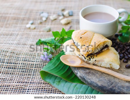 Coffee with snacks on a wooden table in the garden in the mornin - stock photo
