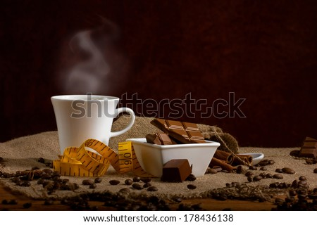 coffee with steam in white cup, chocolate, coffee beans and cinnamon sticks , measure tape on sacking on dark brown background