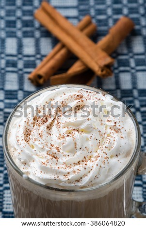 coffee with whipped cream and cinnamon on table