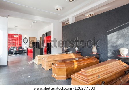 Coffins and urns in a funeral office - stock photo