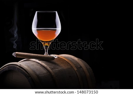 Cognac and Cigar on black background with wooden vintage barrel - stock photo