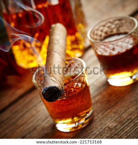 Cognac and cigar on wooden background - stock photo