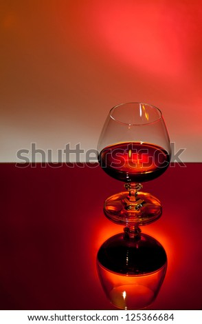 cognac glass on red background - stock photo