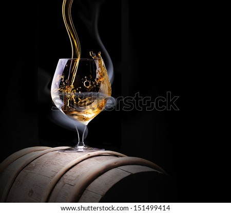 Cognac glass shrouded in a smoke on a black background - stock photo