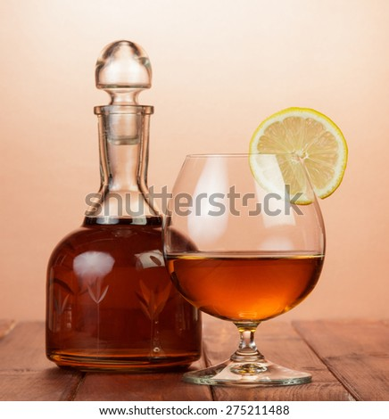 Cognac in bottle and glass with lemon - stock photo