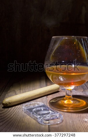 Cognac in glass and cigar on a wooden surface