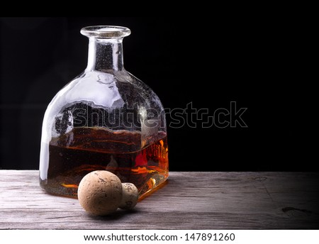 Cognac or brandy on a wooden vintage table with black background