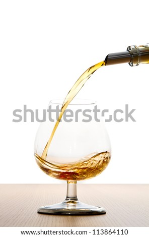 cognac pour into the glass - stock photo
