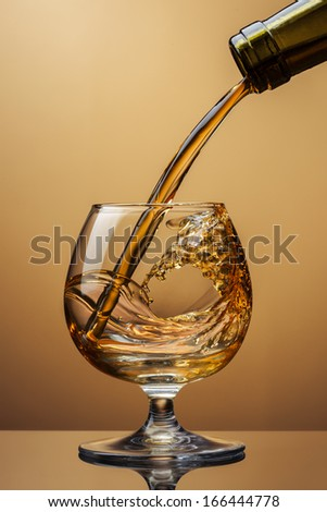 Cognac pouring from bottle into glass with splash on brown background - stock photo