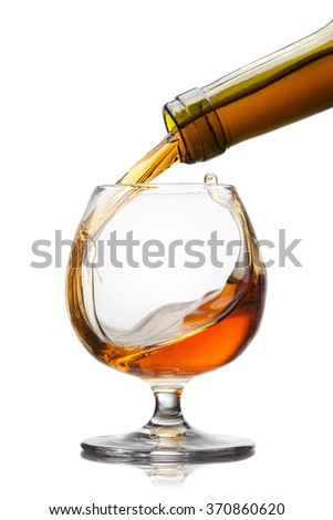 Cognac pouring into glass with splash isolated on white background