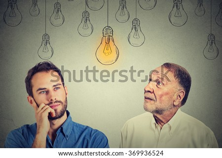 Cognitive skills concept, old man vs young person. Senior man and young guy looking at bright light bulb isolated on gray wall background  - stock photo