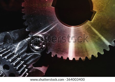 cogwheels, gears and ball-bearings in various metallic shades of colors - stock photo