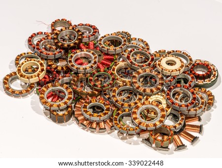 Coil assemblies from motors in card drives and optical drives. The coils are in a pile to be recycled. They are wound with copper wire with red and clear enamel. View is from the top. - stock photo