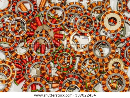 Coil assemblies from motors in hard drives and optical drives. The coils are in a pile to be recycled. They are wound with copper wire with red and clear enamel. Focus is near the middle. - stock photo