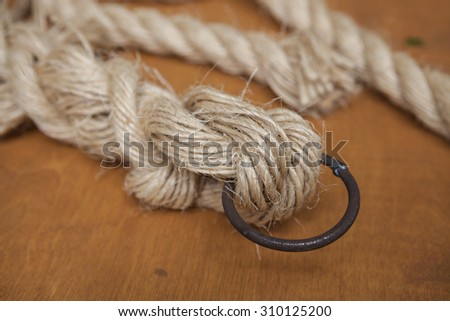Coil of rope with a marine unit, and an iron ring - stock photo