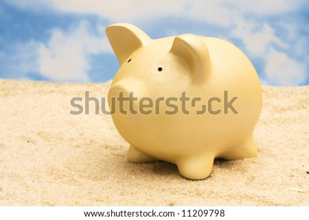 Coin bank on sand with copy space