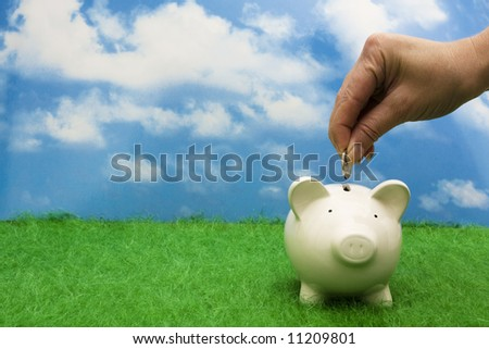 Coin bank sitting on grass with hand putting in a coin - stock photo