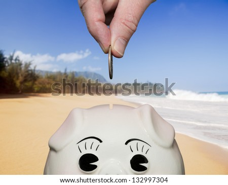 Coin being inserted into piggy bank with fingers illustrating saving for vacation on beach - stock photo