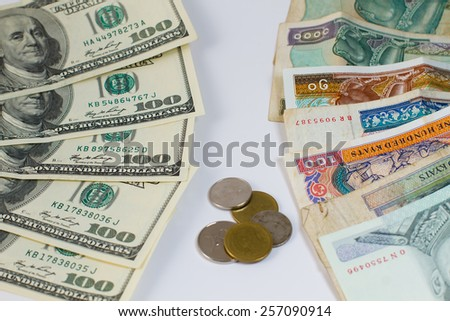 Coin between the hundred-dollar bills and other currencies. - stock photo