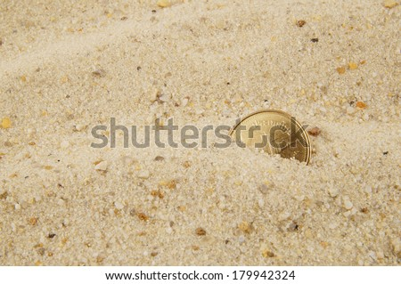 Coin buried in the sand with room for text - stock photo