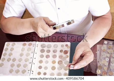 Coin collector is looking at his collection through a magnifying glass - stock photo