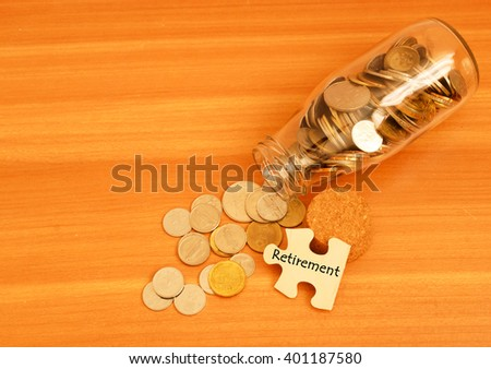 coin in jar and puzzle with word retirement - stock photo