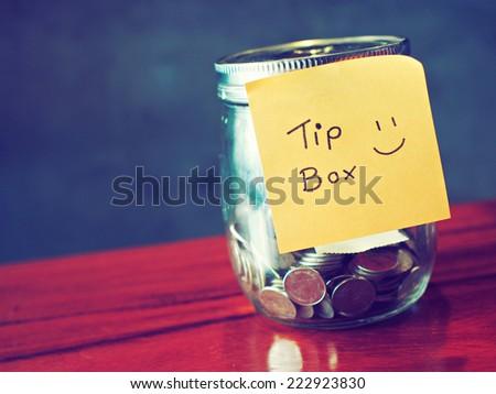 coin in money jar Tip box - stock photo