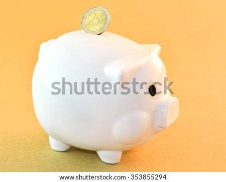 Coin of two euro putting into piggy bank on yellow background