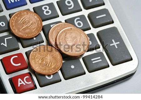 coin on calculator - stock photo